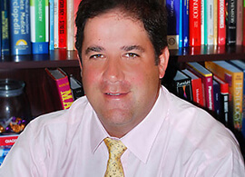 Dr. Andrew Brooks looks at the camera in front of a wall of books.