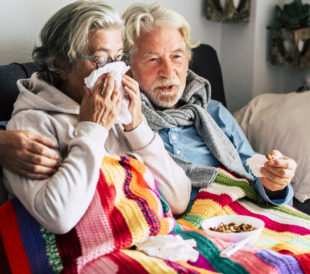 A man and a woman sit on a couch. The woman blows her nose while wrapped in a blanket, and the man's arm is around her shoulders