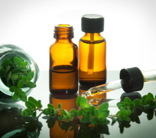 Essential oil bottles with fresh oregano leaves