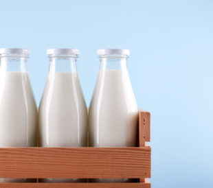 Three glass milk bottles in a wooden crate on a blue background