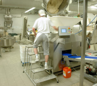 A dough manufacturing worker climbs a ladder next to a large machine.
