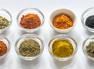 Eight small glass bowls filled with spices and herbs. Image by Alexander Prokopenko/shutterstock.com