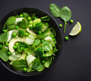 A salad composed of peas, spinach, broccoli and melon sits in a black bowl on a black table.