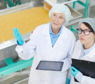Two women in white lab coats look up while talking to one another.