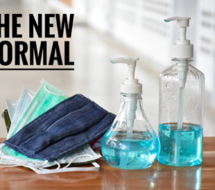 "The words ""The New Normal"" sit above a pile of masks and two bottles of hand sanitizer, symbolizing the challenges of socially distanced scientific work in labs"