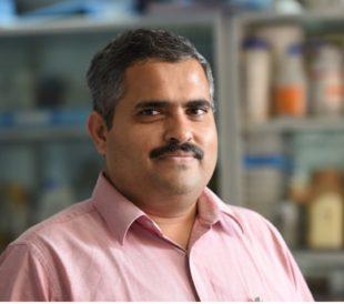 Dr. Dalal smiles at the camera in his lab