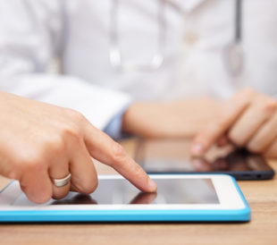 Doctor sharing data on a tablet. Image: Bacho/Shutterstock.com
