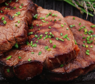 BBQed red meat with thyme on a barbecue pan