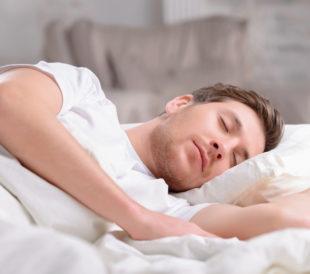 Man sleeping under white covers