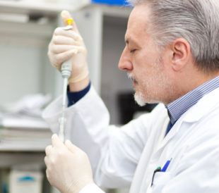A light-skinned man with gray hair in a white lab coat carefully pipettes reagents into a test tube.