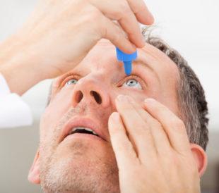 man putting drops in his eye