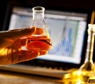 Scientist doing research and holding a beaker. Image: Brian Goodman/Shutterstock.com.